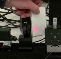 Un signal lumineux peut transmettre des informations, d'un MP3 à des enceintes. Néanmoins, l'obstruction du signal, ici par un matériau, coupe la transmission de données, et donc l'émission du son en fin de chaîne.